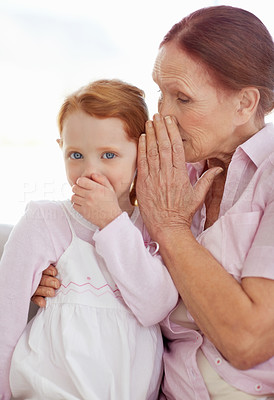 Buy stock photo Portrait of grandmother telling a secret to her granddaughter
