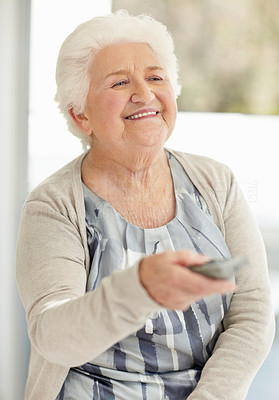 Buy stock photo Shot of a happy mature woman holding remote control while watching television