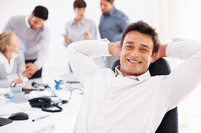 Buy stock photo Smiling business man reclines back in his chair with colleagues discussing in background