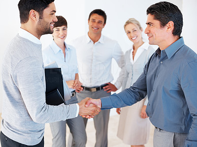 Buy stock photo Successful business partners shaking hands with team in background