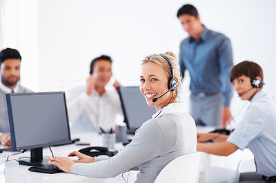 Buy stock photo Beautiful customer service representative using computer with colleagues in background