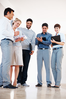 Buy stock photo Full length of business people standing together at corridor while discussing work