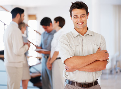 Buy stock photo Confident business man smiling with colleagues discussing in background
