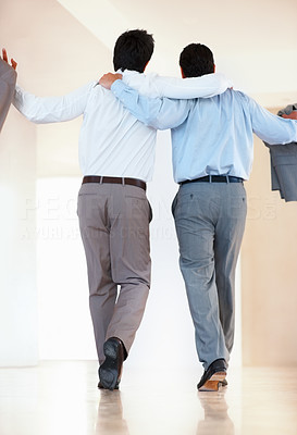 Buy stock photo Rear view of business colleagues walking with arms around