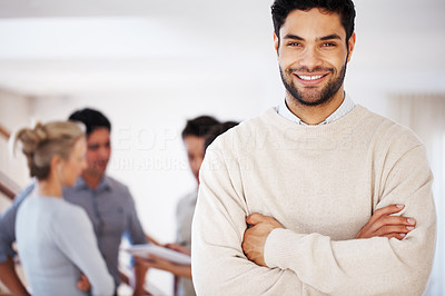 Buy stock photo Portrait of handsome young business man smiling with hands folded and colleagues in background