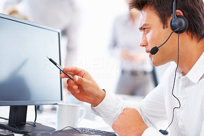 Buy stock photo Call center executive in headset pointing at computer with colleagues in background