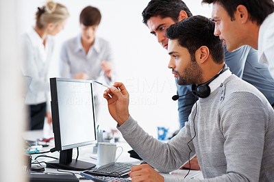 Buy stock photo Three business men working on computer with colleagues in background