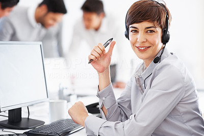 Buy stock photo Female call center executive sitting in front of computer with colleagues in background