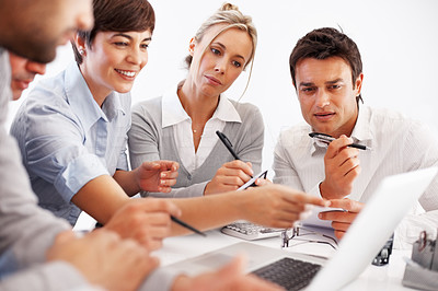 Buy stock photo Business woman points at laptop screen while discussing with team in meeting