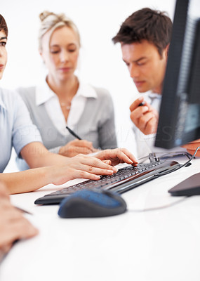 Buy stock photo Female executive working on computer with colleagues in background
