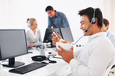 Buy stock photo Male customer executive having fruit salad with colleagues in background