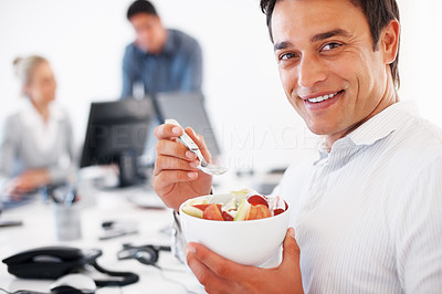 Buy stock photo Closeup of handsome business man eating fruit salad with colleagues discussing in background