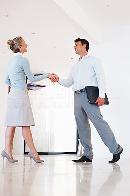 Buy stock photo Full length of successful business man and woman shaking hands in the corridor