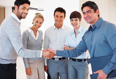Buy stock photo Two business male executives greeting each other in front of colleagues