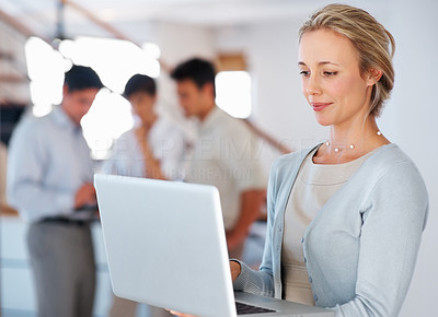 Buy stock photo Business woman using laptop with colleagues discussing in background