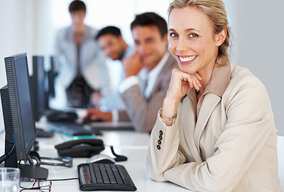 Buy stock photo Portrait of business woman sitting with hand on chin and giving you an attractive smile with colleagues in background