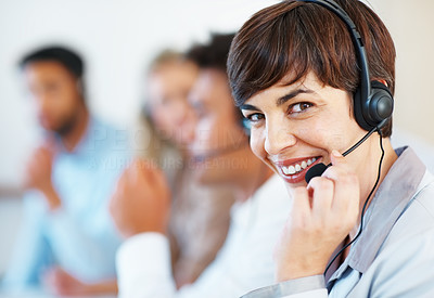 Buy stock photo Closeup of beautiful customer service executive smiling with colleagues in background