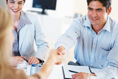Buy stock photo Smart business man sitting at table and shaking hands with colleague during meeting