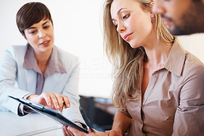 Buy stock photo Colleagues sitting at table during business meeting and going through clipboard