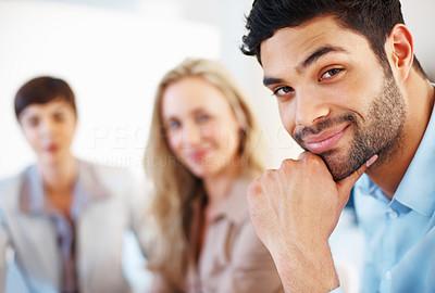 Buy stock photo Closeup of handsome business man smiling with hand on chin and colleagues in background