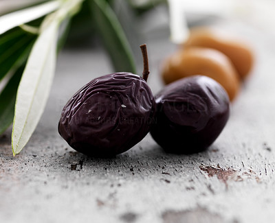 Buy stock photo Closeup of dried black olives on floor with leaves