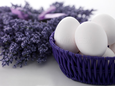 Buy stock photo Easter eggs in wicker basket with bunch of purple spring flowers on white background