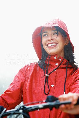 Buy stock photo Smiling woman in raincoat on bike