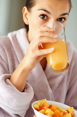Buy stock photo Attractive woman drinking juice and holding bowl of fruit