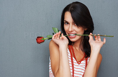 Buy stock photo Flirtatious woman posing while holding rose between teeth