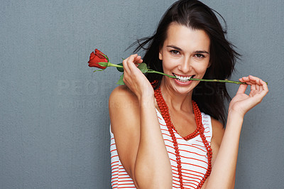 Buy stock photo Pretty woman posing with rose between teeth
