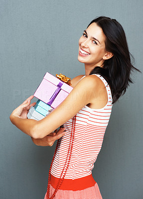Buy stock photo Side view of woman holding presents while smiling agaisnt a grey background