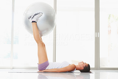 Buy stock photo Side-view of young woman training with a fitness ball