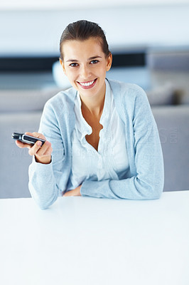 Buy stock photo Portrait of smiling young woman with mobile phone at home