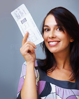 Buy stock photo Closeup portrait of beautiful woman holding boarding pass on colored background