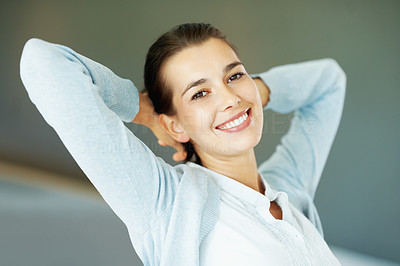 Buy stock photo Closeup of smiling young woman sitting with hands behind head