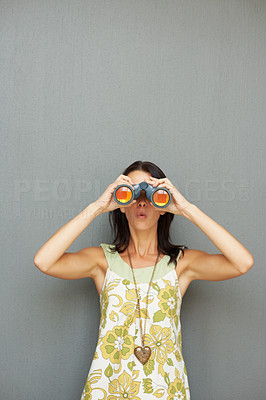 Buy stock photo Surprised young woman looking through binoculars
