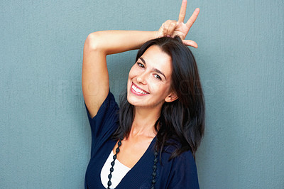 Buy stock photo Portrait of smiling young woman keeping two fingers above head