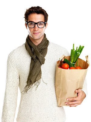 Buy stock photo Portrait of handsome hip young man in glasses holding a paper shopping bag on white background
