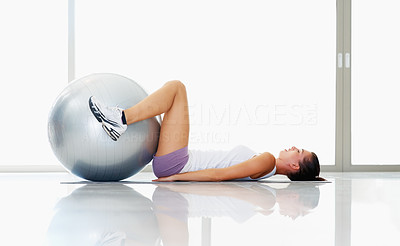 Buy stock photo Side view of active young woman training on exercise ball