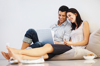 Buy stock photo Relaxed young couple using laptop and smiling
