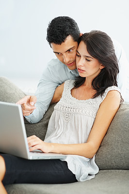 Buy stock photo Portrait of young woman with handsome man pointing at laptop
