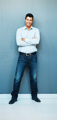 Buy stock photo Full length of happy young man with hands folded against the wall