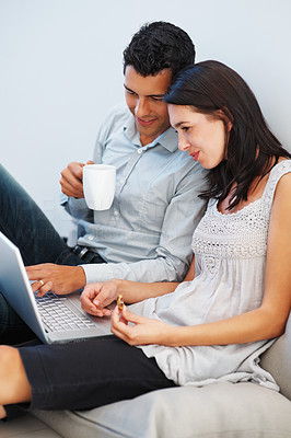 Buy stock photo Young couple having tea and cookies while using laptop