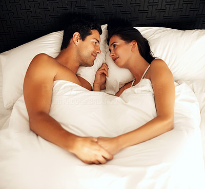 Buy stock photo Top view of happy young couple holding hands in bed