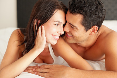 Buy stock photo Young smiling couple looking at each other while lying in bed