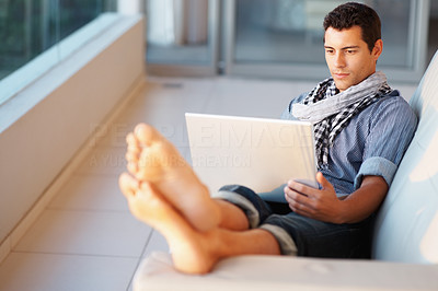 Buy stock photo Casual urban young man using laptop at home