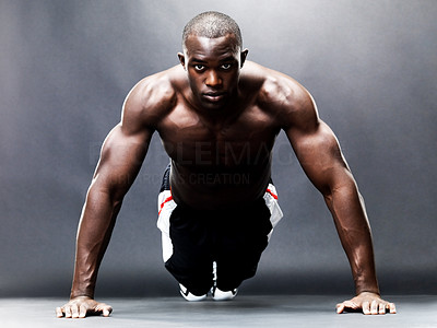 Buy stock photo Portrait of a healthy young guy doing push ups against a grunge background