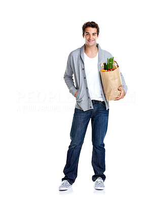 Buy stock photo Portrait of a handsome young man holding a bag full of groceries on white