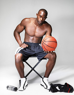 Buy stock photo Portrait of young basketball player sitting on a stool with a ball in hand on grey background