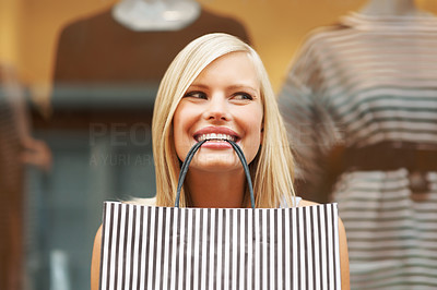 Buy stock photo Pretty woman smiling cheekily with a shopping bag in her mouth in front of a clothing store